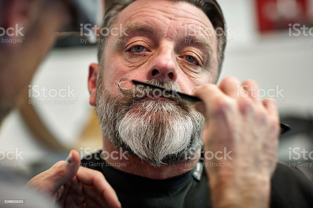 Barber working on mature man's mustache stock photo