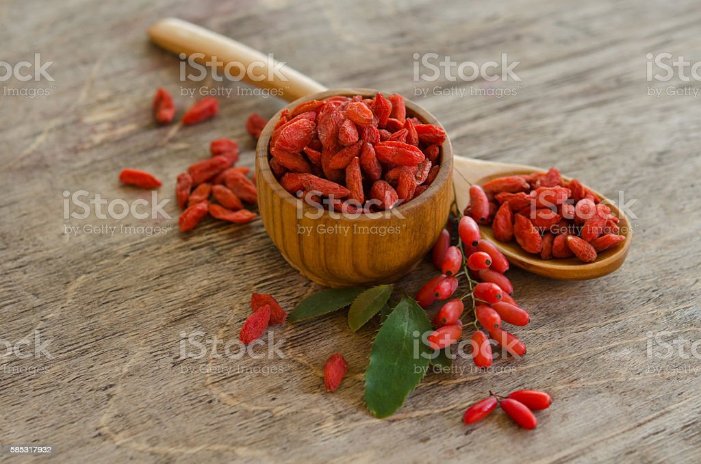 barberries and goji berries isolated on wooden background stock photo