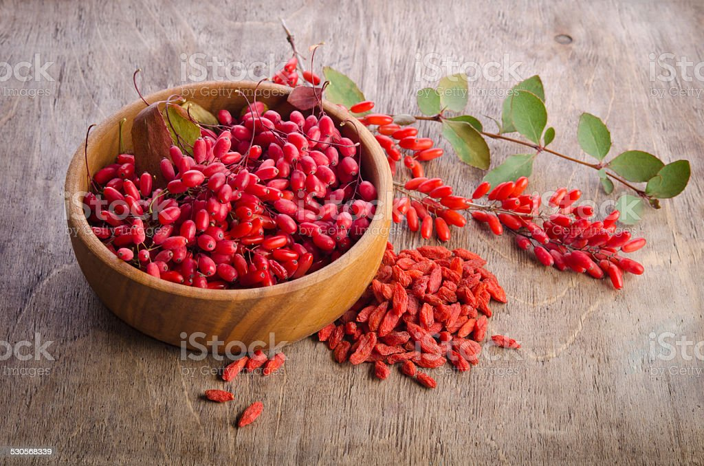 Barberry with leaves and dry goji berries on wooden background stock photo