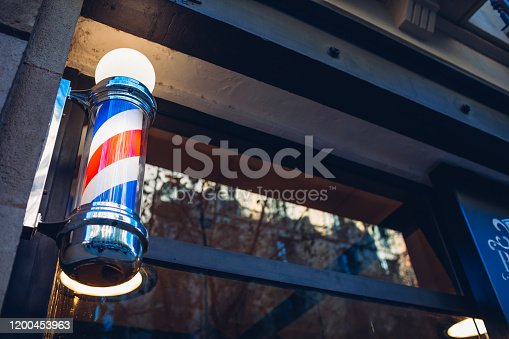 istock Barber's pole on a barbershop wall in the evening on a street of Barcelona, Spain 1200453963