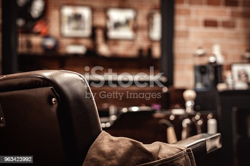 istock Barbershop chair and blurred background 963423992