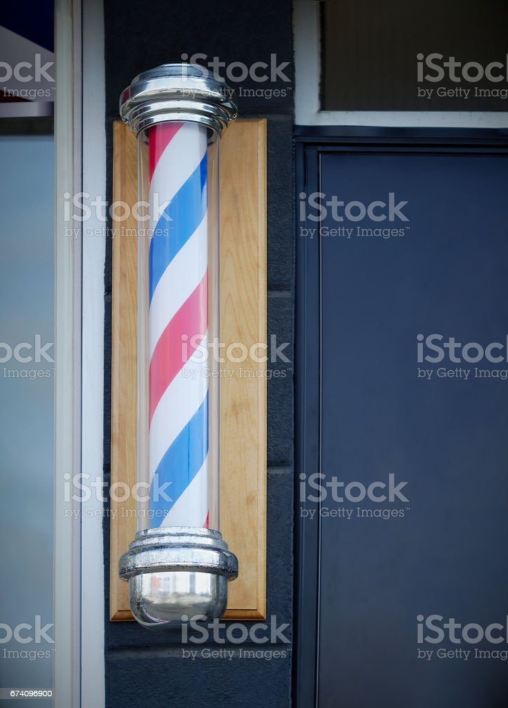 barbershop hairdresser traditional sign red blue and white spinning pole stock photo