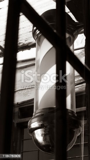 istock Barbershop pole light outside the store in a sepia color picture 1184780909