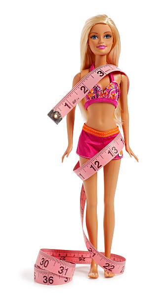 barbie puppe in einem bikini mit maßband gewickelt - barbiekleidung stock-fotos und bilder