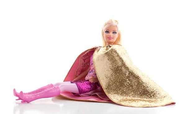 barbie puppe mit gold cape auf weißem hintergrund - barbiekleidung stock-fotos und bilder