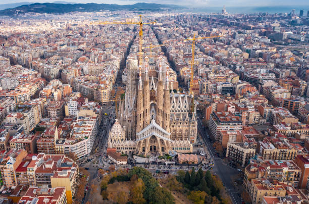 Barcelona; aerial view of Temple Expiatori de la Sagrada Familia Aerial; drone view of main Gaudi project Sagrada Familia Temple; majestic building towering over the rooftops of Eixample district; long construction of the temple