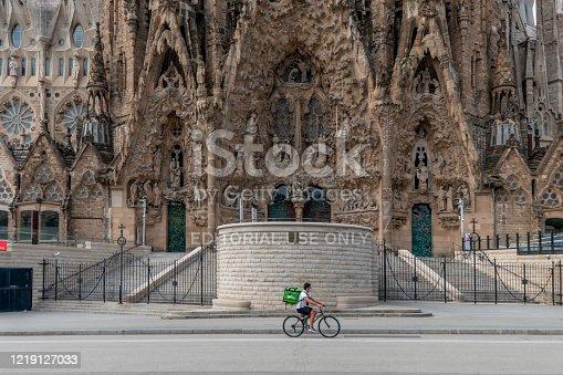 Barcelona, Catalonia / Spain: 04 09 2020: Delivery riders in front of the Sagrada Familia in the city of Barcelona during confinement in the city of Barcelona during the covid-19 coronavirus pandemic