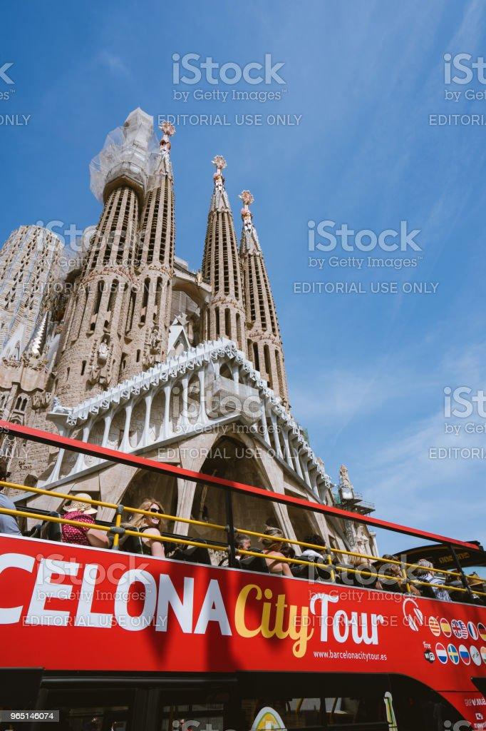 Barcelona city tour touristic bus near famous Sagrada Familia Basilica yet not finished work of Catalan architect Antoni Gaudi royalty-free stock photo