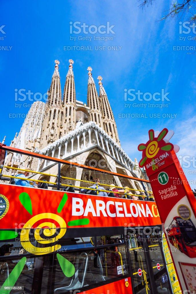 Barcelona city tour touristic bus with tourists near famous Sagrada Familia Basilica. Unfinished work of Catalan architect Antoni Gaudi royalty-free stock photo