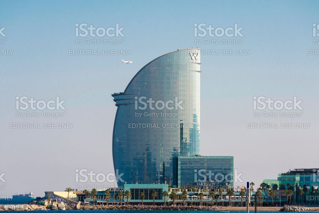 W Barcelona hotel with an airplane flying next to this stock photo