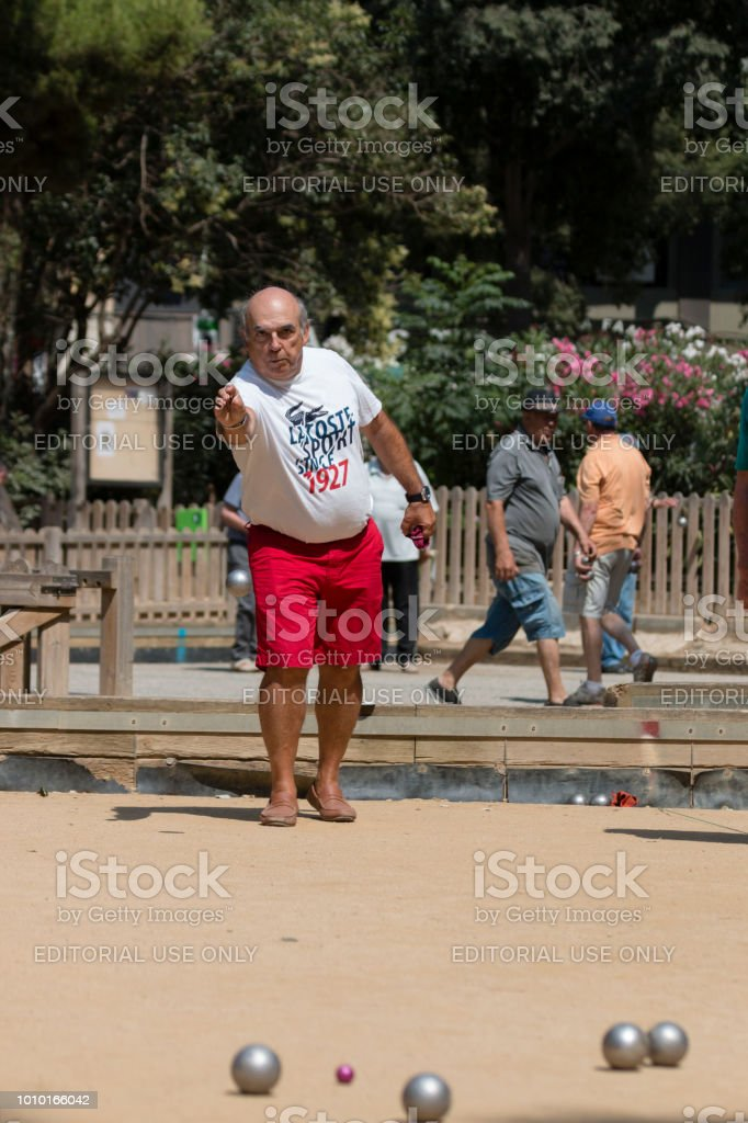 Barcelona, Spain, July 2018:  Local play petanque near Sagrada Familia. Man focused on target before drop metallic ball. stock photo