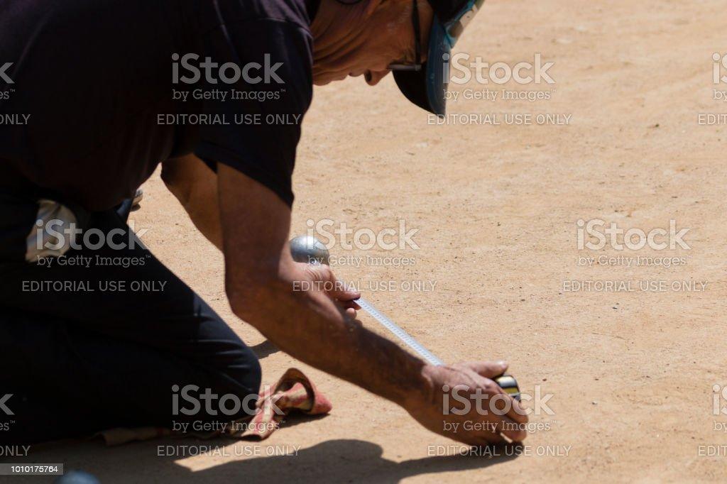 Barcelona, Spain, July 2018:  Local play petanque near Sagrada Familia. Man makes measurements. stock photo