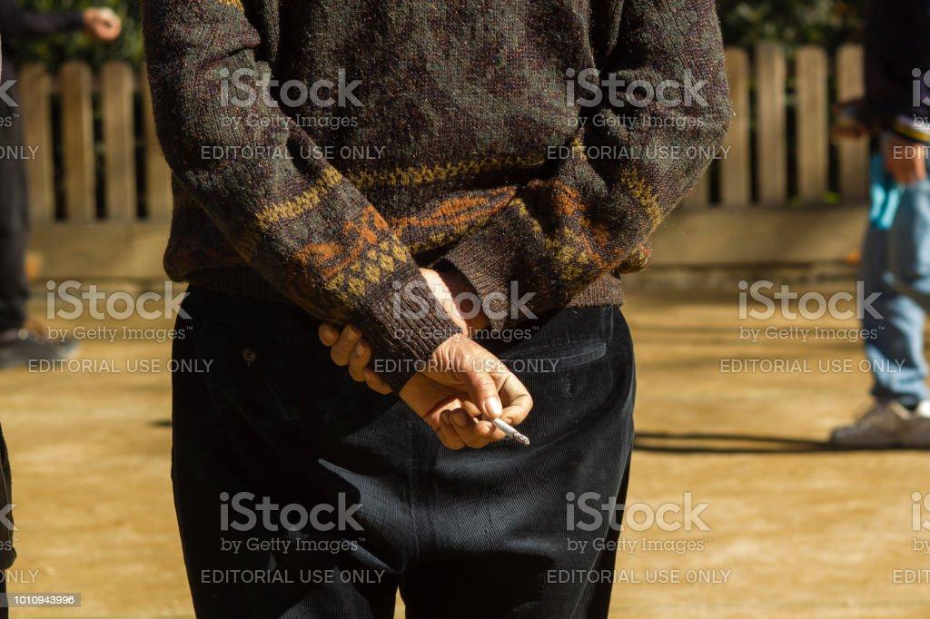 Barcelona, Spain, March 2018:  Elder Man smoking sigarette during petanque game near of Sagrada Familia. stock photo