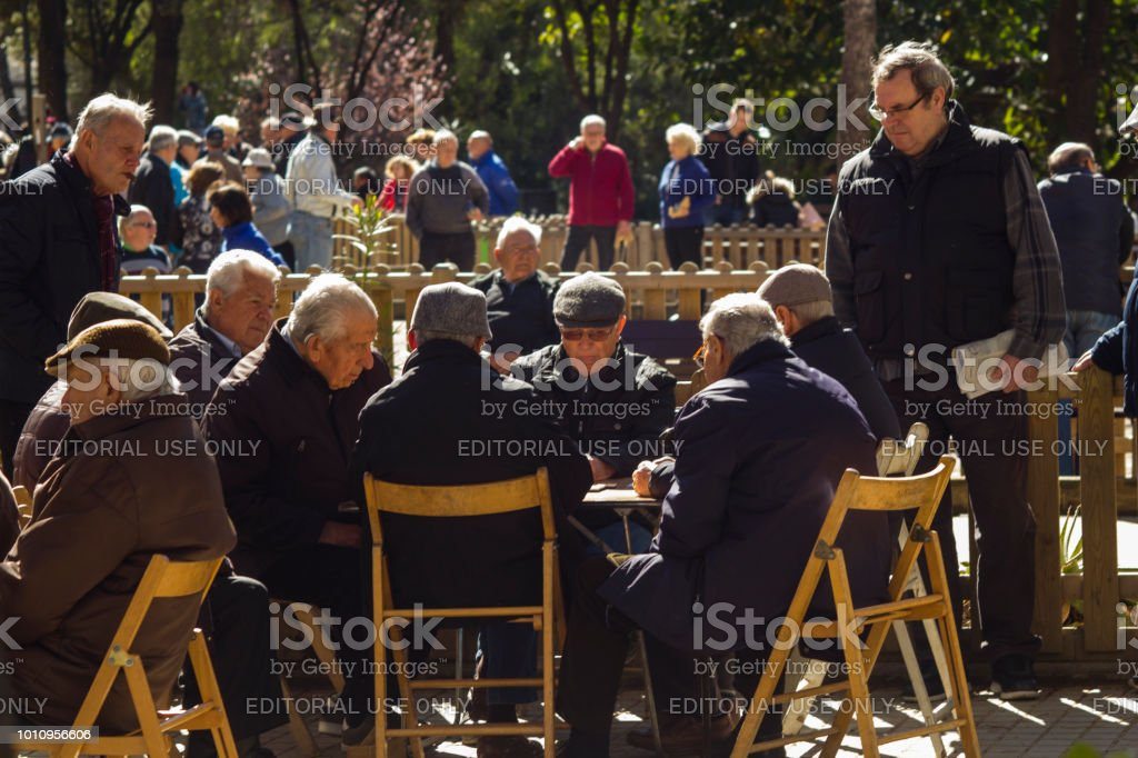 Barcelona, Spain, March 2018:  Local elders relaxing  playing domino. stock photo