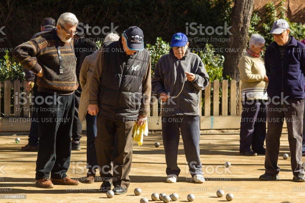 Barcelona, Spain, March 2018:  Locals elders play petanque near Sagrada Familia stock photo