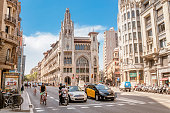 12 JULY 2018, BARCELONA, SPAIN: Barcelona street with high building and road traffic