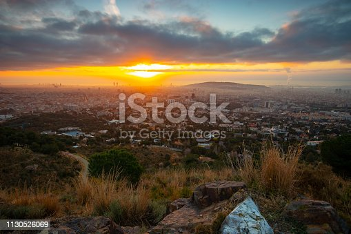 Barcelona's sunrise during winter, February - Wide angle shot with warm colors in the land and grass