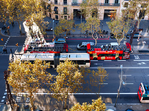 Barcelona Tour Bus Barcelona, Spain - December 05, 2011 : Barcelona Tour Buses with people at the second open roof floor are riding at the Passeig de Gracia in centre of Barcelona. View from the top of the Casa Mila (Pedrera), designed by Antonio Gaudi passeig de gracia stock pictures, royalty-free photos & images