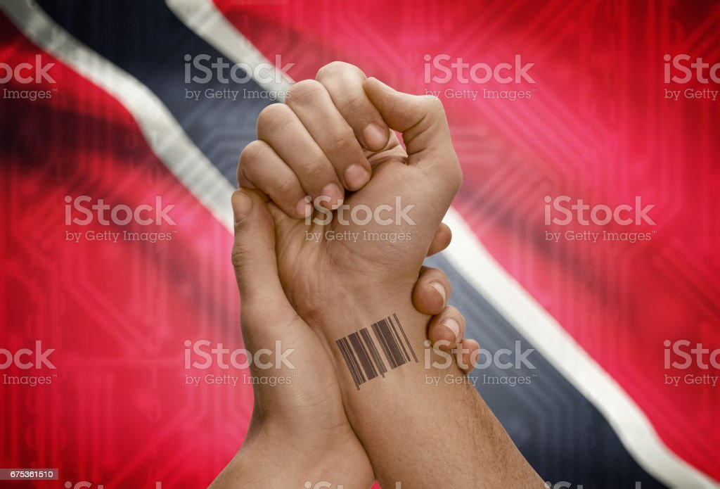 Barcode ID number on wrist of dark skinned person and national flag on background - Trinidad and Tobago stock photo
