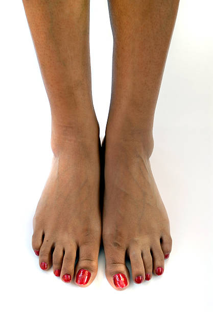 Bare African American feet with red nail polish stock photo