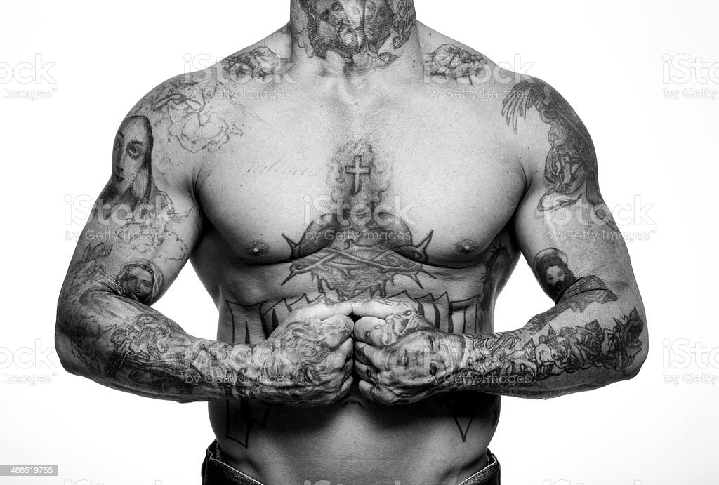 Bare chested man with religious tattoos and closed fists stock photo