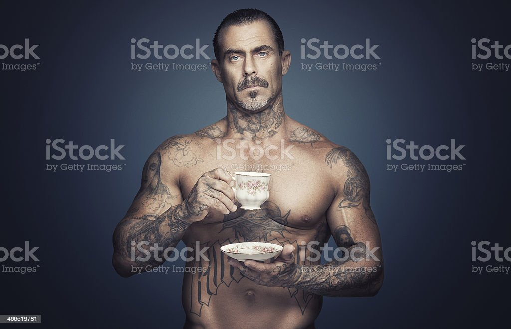 Bare chested man with tattoos holding a cup of tea. stock photo