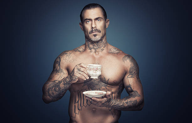 bare chested man with tattoos holding a cup of tea. - 紋身 人體裝飾 個照片及圖片檔