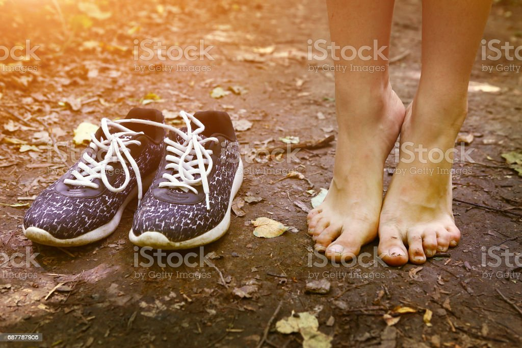 bare feet and shoes on forest path stock photo