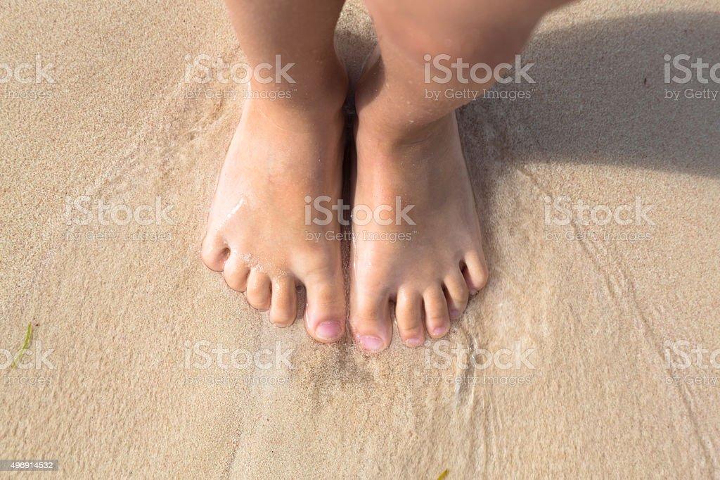 Bosych stóp małe dziecko stoją w piasku na plaży – zdjęcie