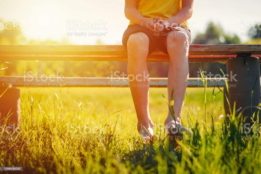 Bare feet of a boy hang down from a bench – zdjęcie