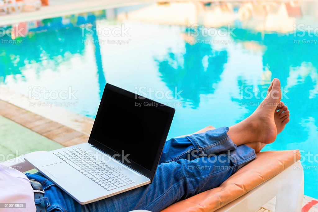 bare feet of a businessman on vacation pool stock photo