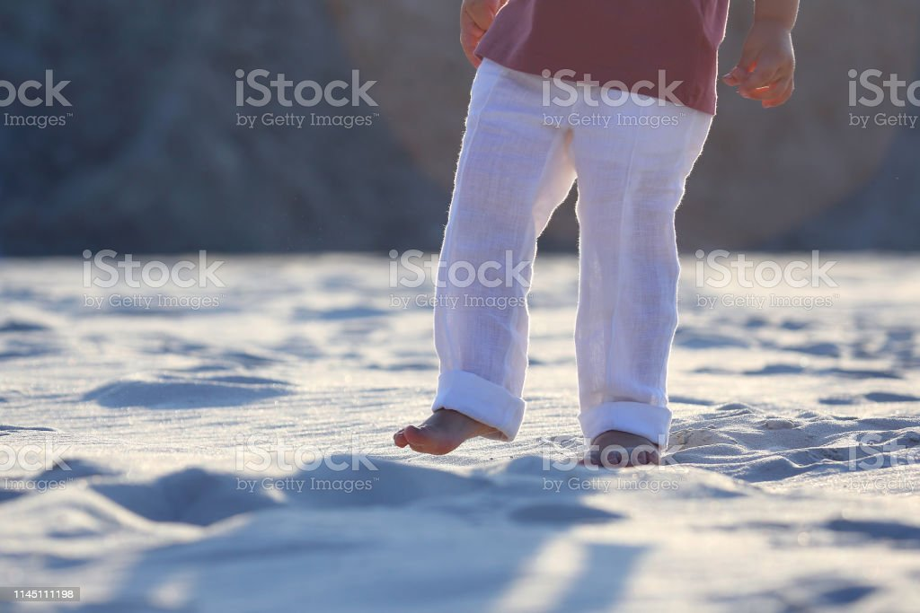 bare feet of a child in white pants on the sand – zdjęcie