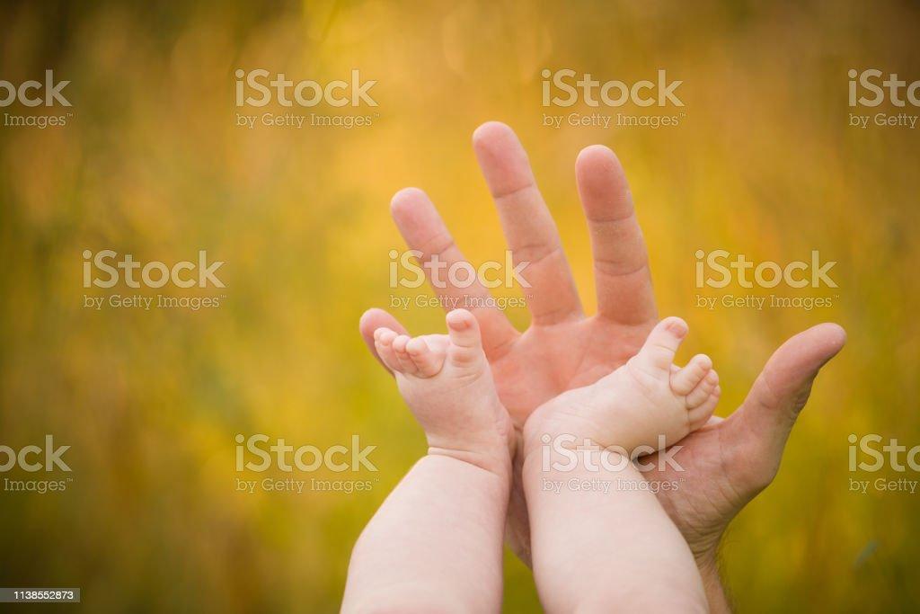 Yaz arka planda sevimli bir bebeğin çıplak ayaklar. Çiftlikte çocukluk. Küçük bir bebeğin çıplak ayakları. Anne Bebek ayakları tutuyor. stok fotoğrafı
