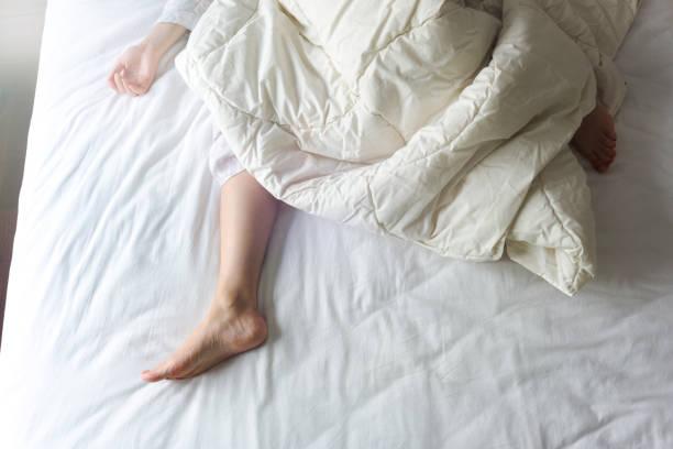 白いベッドの上の若い女性の素足 ストックフォト