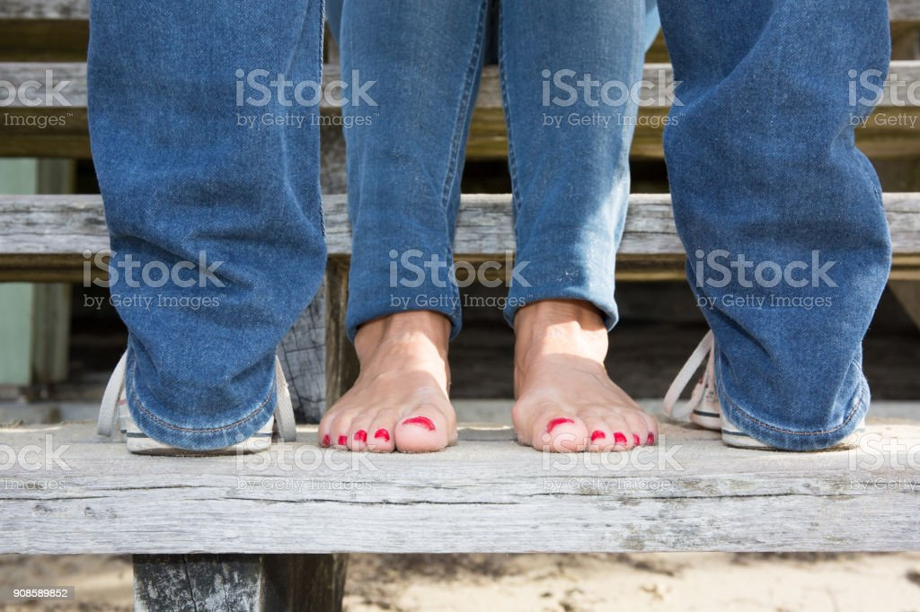 Bare feet of female lovers on wooden stairs – zdjęcie