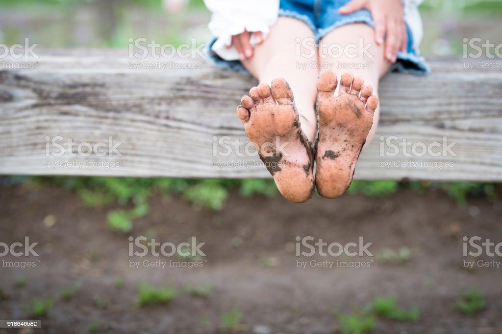 Bare feet of muddy children stock photo