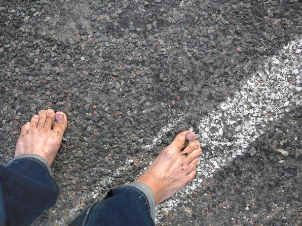 Bare Feet On Asphalt Road stock photo