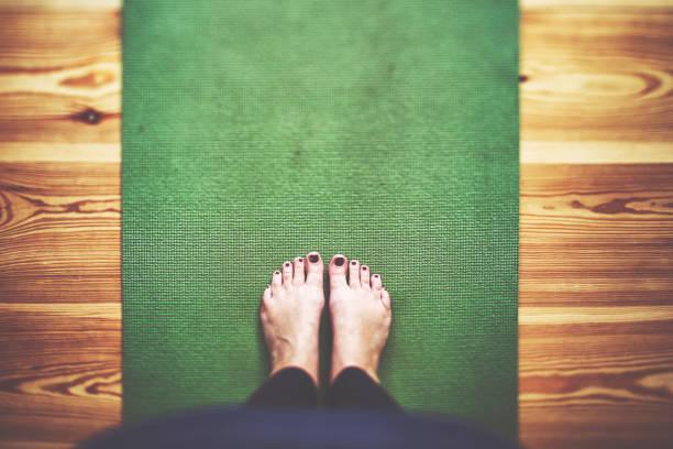 Bare feet on the green Yoga mat stock photo