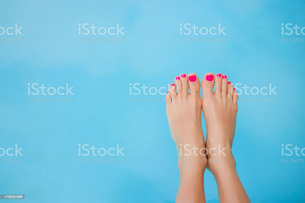 Bare feet over swimming pool stock photo