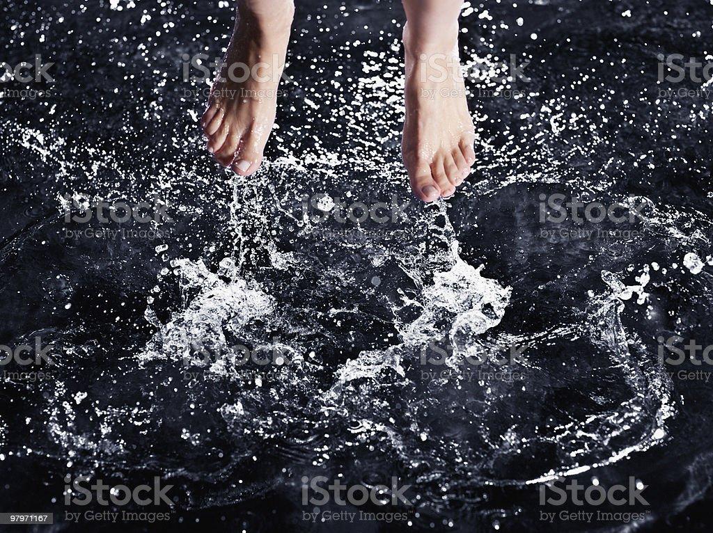 Bare feet splashing in water royalty-free stock photo