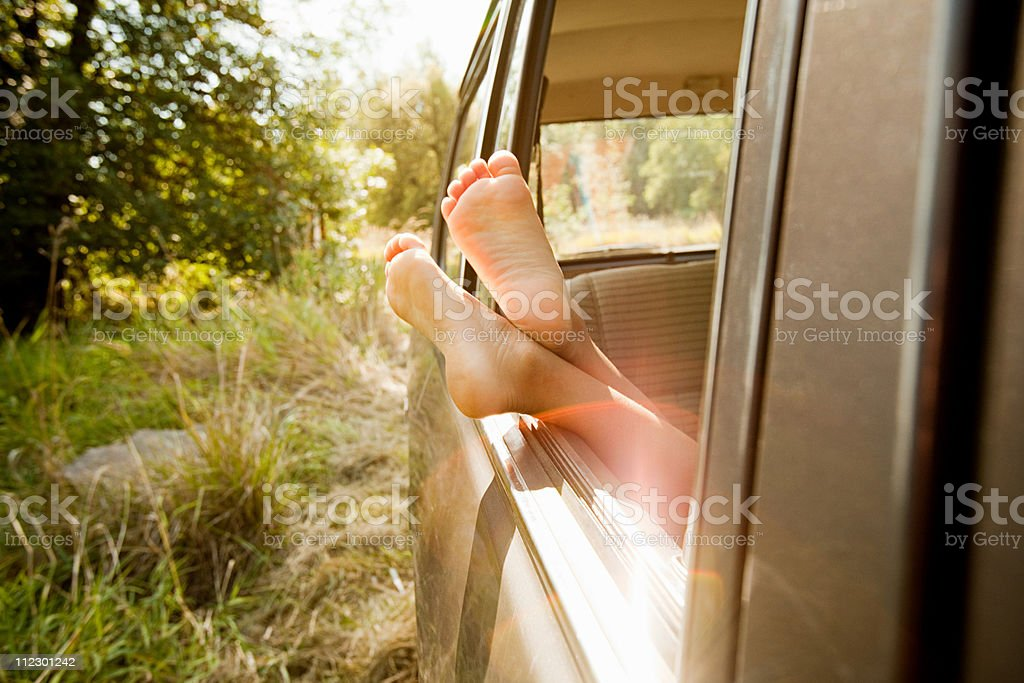 Bare feet sticking out of a car window royalty-free stock photo