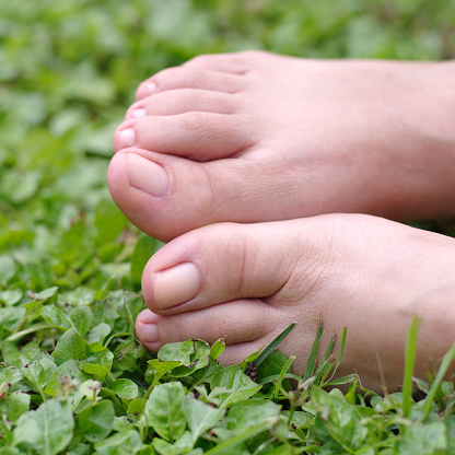 Bare Female Feet On Grass With Natural Nails — стоковые фотографии и другие картинки Взрослый