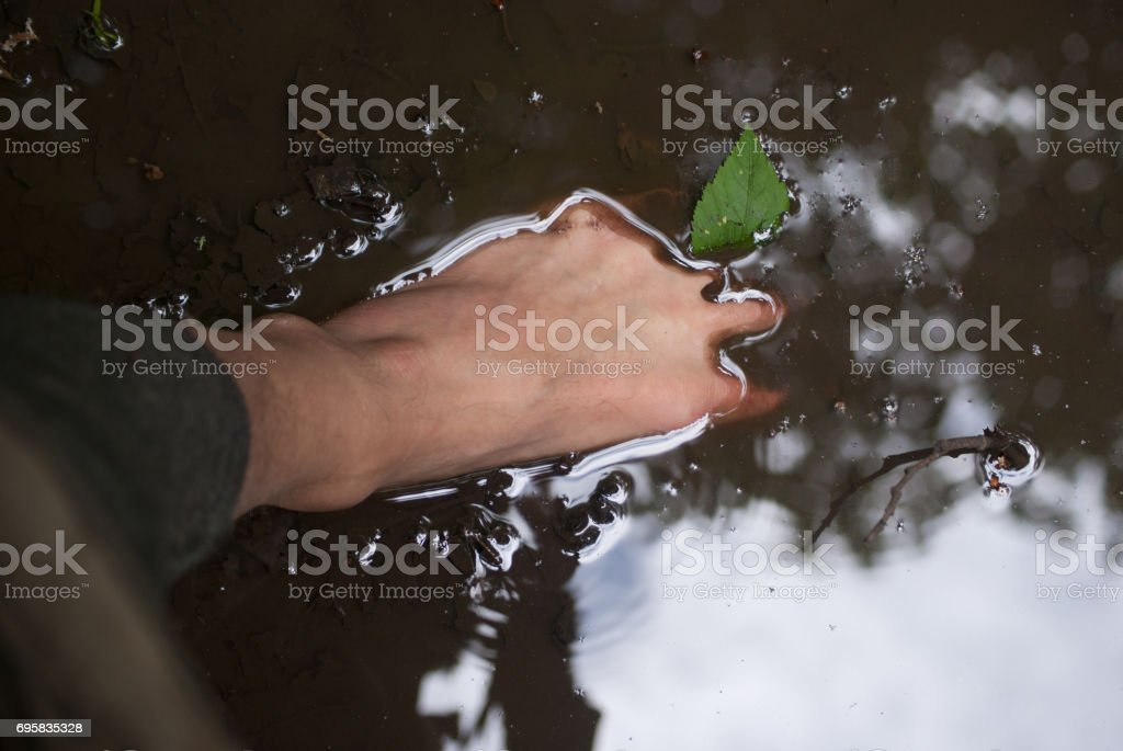Bare foot in a puddle with reflection of trees and sky stock photo