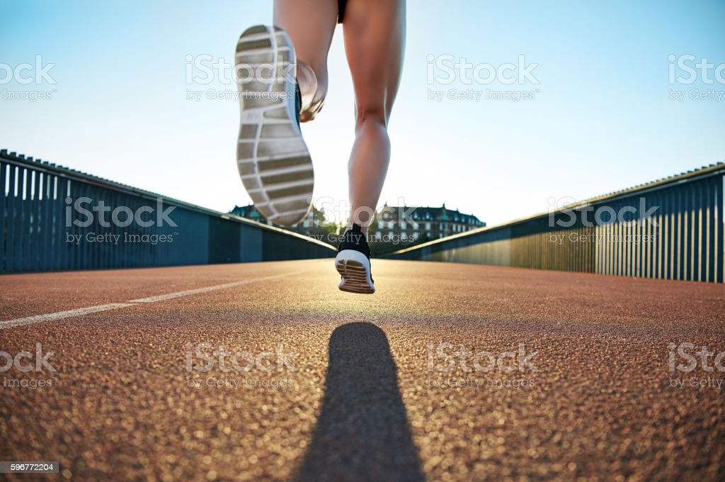 Bare legged jogger bounds towards apartments stock photo