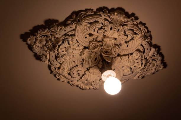 Bare light bulb extending from an extremely ornate cast plaster ceiling medallion Bare light bulb extending from an extremely ornate cast plaster ceiling medallion, horizontal aspect plaster ceiling design stock pictures, royalty-free photos & images