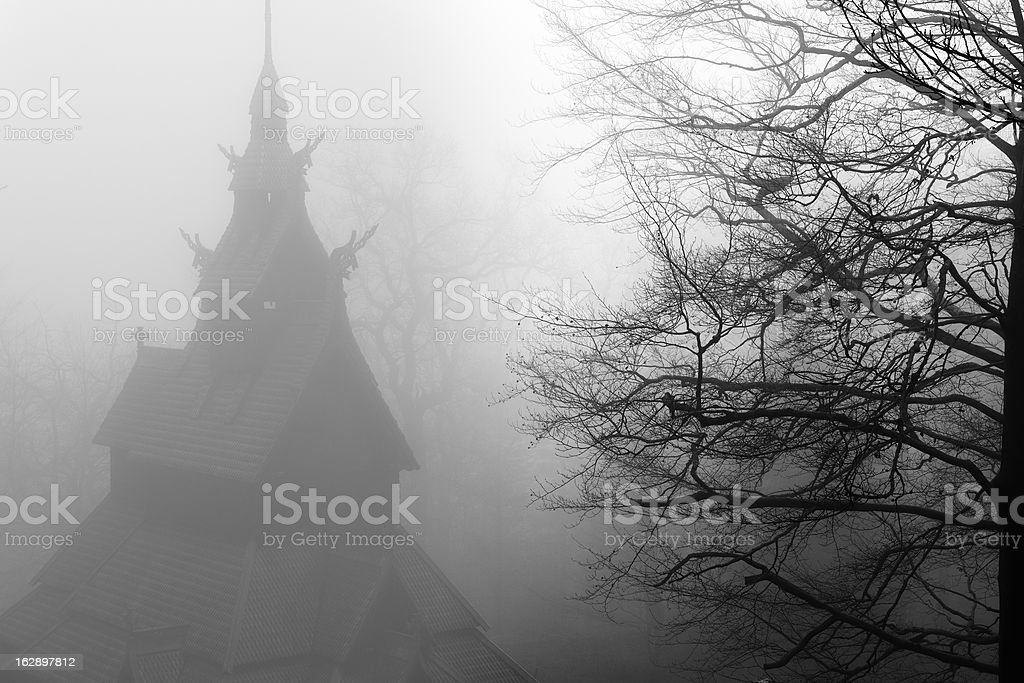 Bare naked tree and stave church on foggy winter day stock photo
