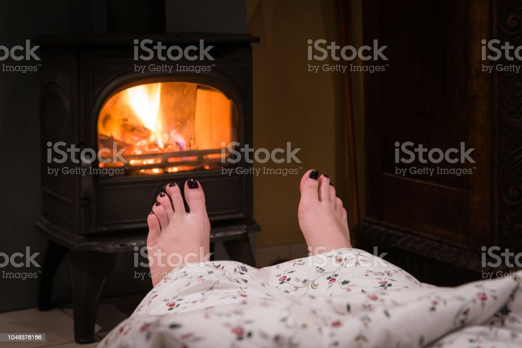 Bare woman feet by the cozy fireplace. Woman relaxes by warm fire...