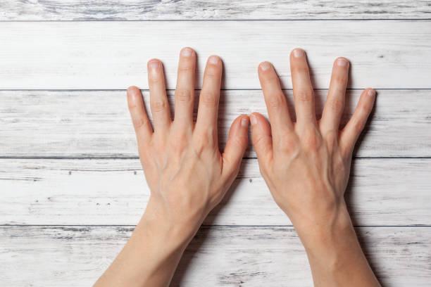 mani nude della donna con unghie corte che giaceno piatte sul tavolo. - bassino foto e immagini stock