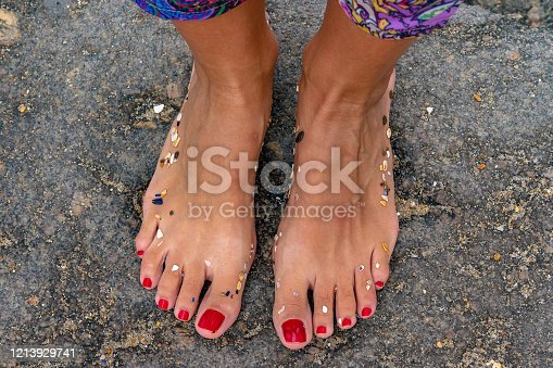 Female feet with red nail polish and colorful pants on a rocky beach