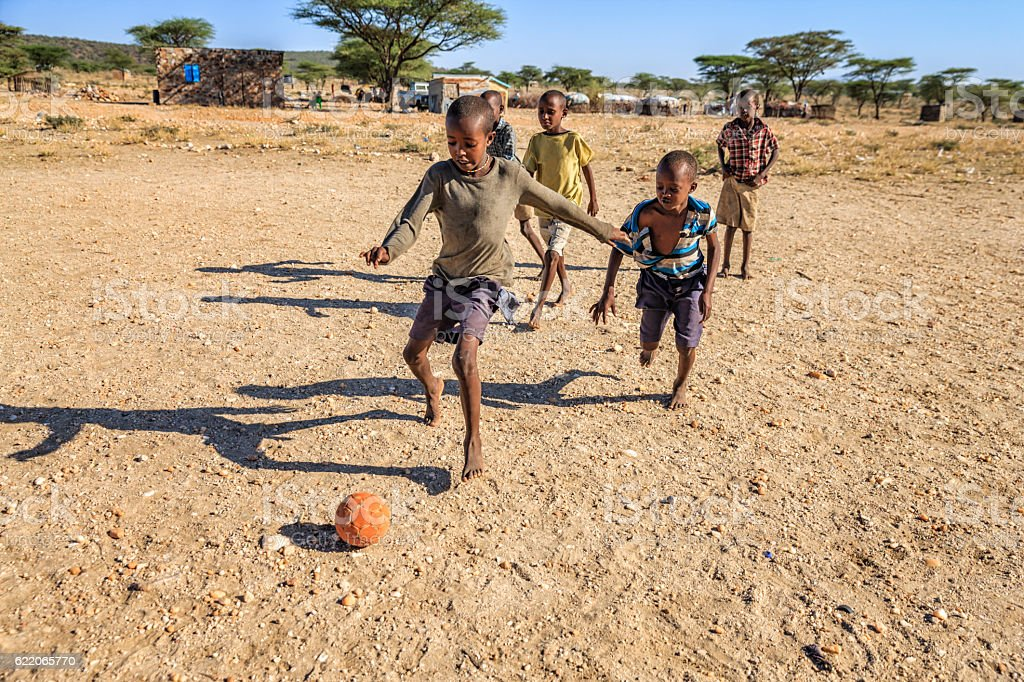 Barefoot African children playing football in the village, East Africa stock photo